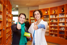 A pharmacy customer and a pharmacist doing a thumbs-up sign